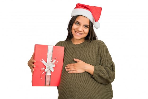 Mulher grávida segurando uma caixa de presente de natal