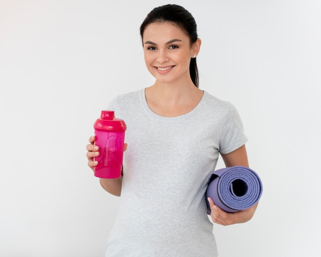 Mulher grávida segurando uma esteira de ginástica e uma garrafa de água