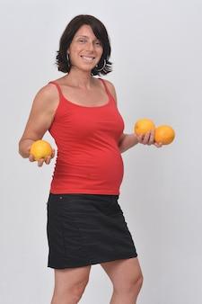 Mulher grávida segurando uma fruta laranja em fundo branco