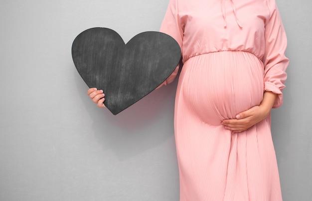 Mulher grávida segurando uma lousa vazia