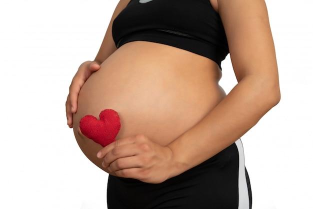 Mulher grávida segurando uma placa de coração na barriga