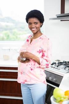 Mulher grávida, segurando, vidro água, em, cozinha