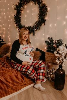 Mulher grávida senta-se de pijama na cama no quarto. manha de natal. interior de ano novo. celebração do dia dos namorados