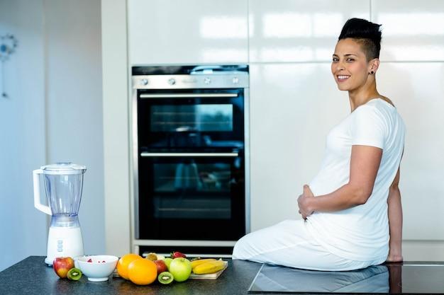 Mulher grávida sentada na bancada da cozinha e sorrindo