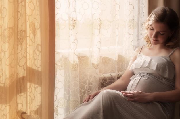 Mulher grávida sentada na janela