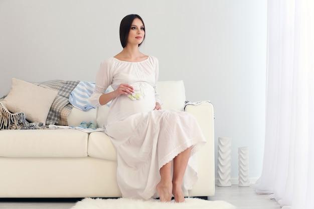 Mulher grávida sentada no sofá com roupas de bebê, na sala