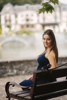 Mulher grávida sentada num banco perto do lago.