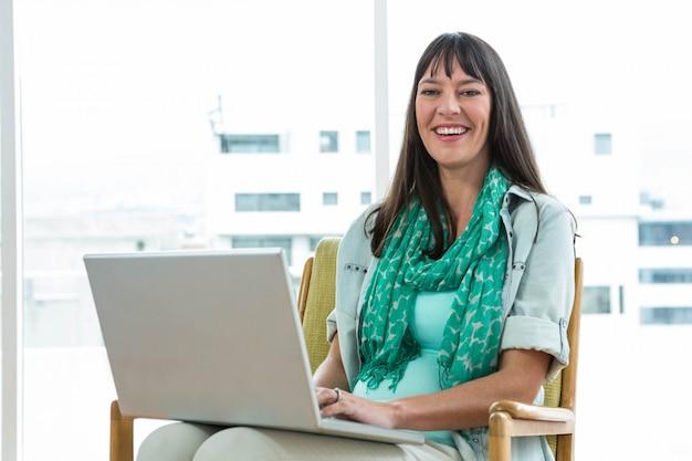Mulher grávida, sentar-se cadeira, e, usando computador portátil, casa