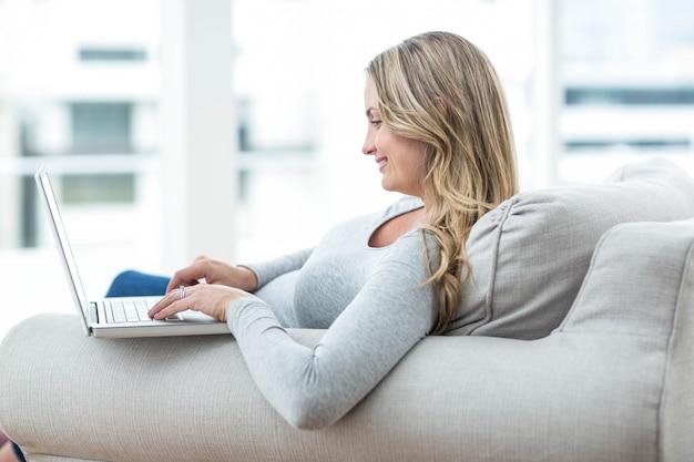 Mulher grávida, sentar sofá, e, usando computador portátil