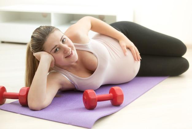 Mulher grávida sorridente deitada na esteira de ginástica com halteres na sala de estar
