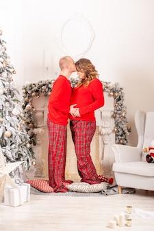 Mulher grávida sorridente e homem se divertem em casa com o interior do natal