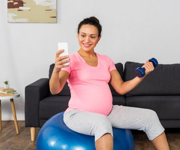 Mulher grávida sorridente em casa treinando com bola e tirando selfie