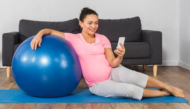Mulher grávida sorridente em casa treinando com bola e usando o celular