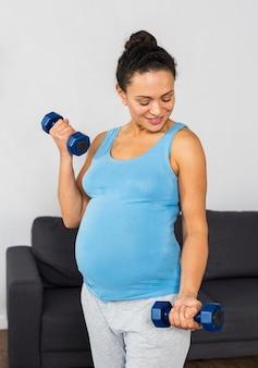 Mulher grávida sorridente em casa treinando com pesos
