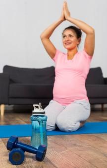 Mulher grávida sorridente fazendo exercícios em casa com garrafa de água e pesos