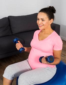Mulher grávida sorridente fazendo exercícios em casa no chão com bola e pesos