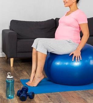 Mulher grávida sorridente fazendo exercícios em casa no chão com bola