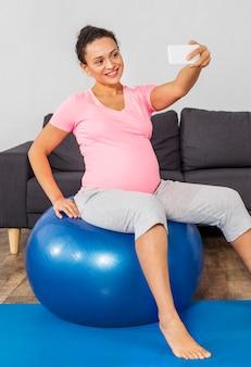 Mulher grávida sorridente fazendo selfie em casa enquanto treina com bola