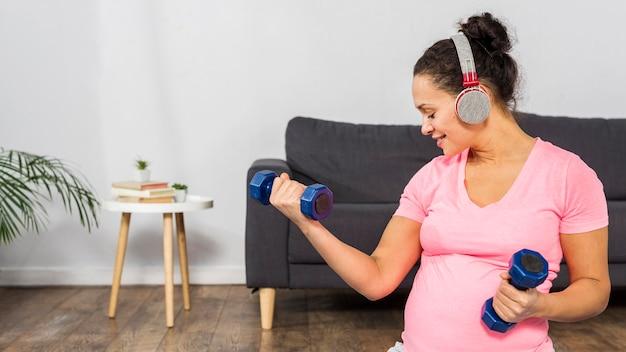 Mulher grávida sorridente ouvindo música em fones de ouvido enquanto se exercita com pesos