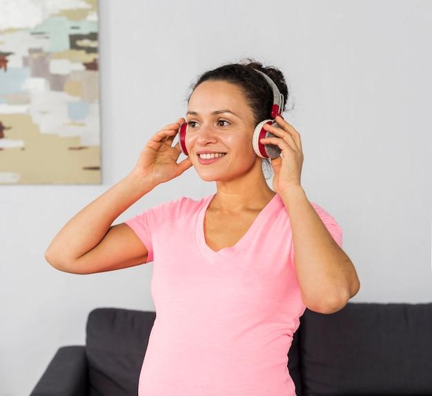 Mulher grávida sorridente ouvindo música em fones de ouvido enquanto se exercita em casa