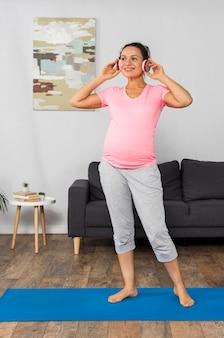Mulher grávida sorridente ouvindo música em fones de ouvido enquanto se exercita