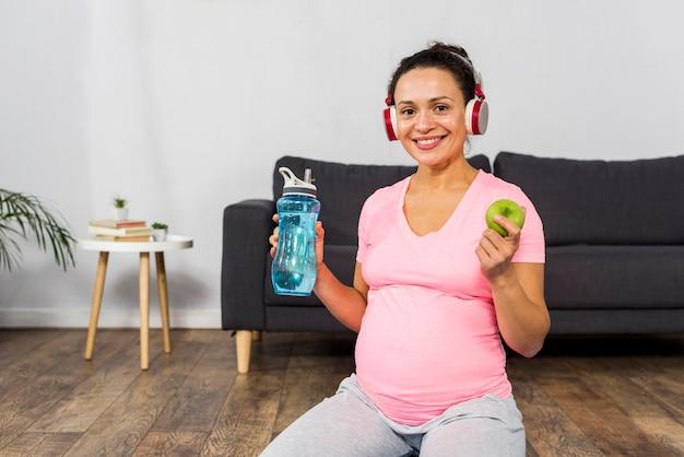 Mulher grávida sorridente ouvindo música em fones de ouvido enquanto segura uma maçã e uma garrafa de água