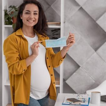 Mulher grávida sorridente segurando máscara médica em casa