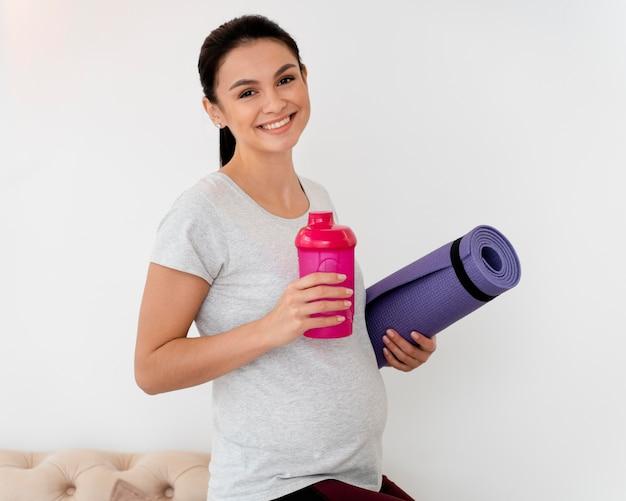 Mulher grávida sorridente segurando uma esteira de ginástica e uma garrafa de água
