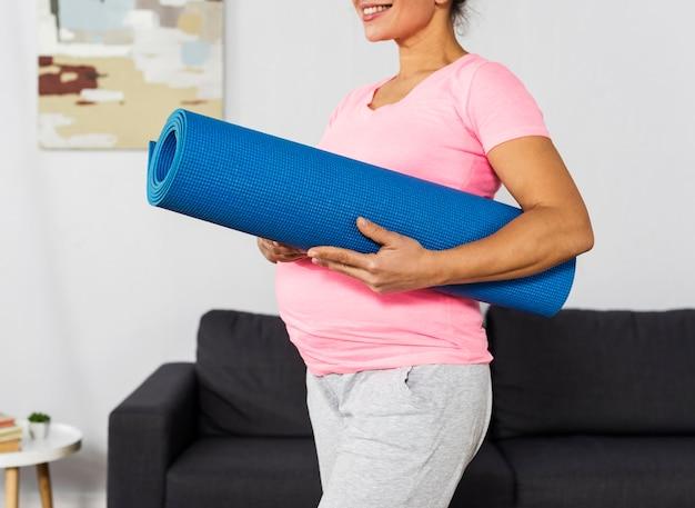 Mulher grávida sorridente segurando uma esteira de ginástica