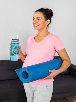 Mulher grávida sorridente segurando uma garrafa de água e um tapete