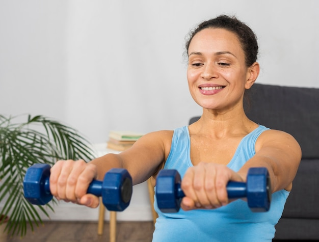 Mulher grávida sorridente treinando com pesos em casa