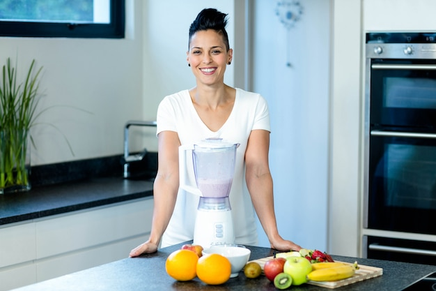 Mulher grávida sorrindo em pé na cozinha com liquidificador e frutas na bancada