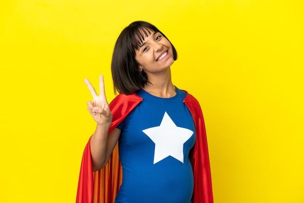 Mulher grávida super-heroína isolada em fundo amarelo sorrindo e mostrando sinal de vitória