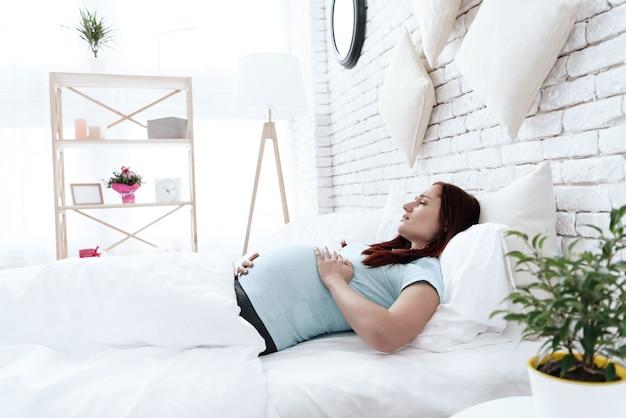 Mulher grávida tem uma dor de estômago ela se sente desconfortável