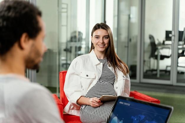 Mulher grávida tendo uma reunião com seu colega de trabalho