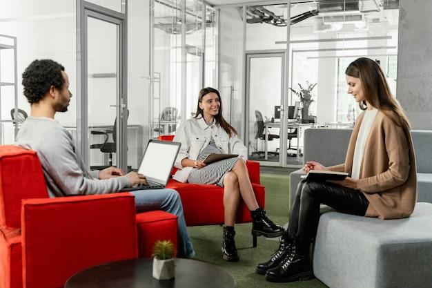 Mulher grávida tendo uma reunião com seu colega de trabalho Foto gratuita
