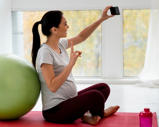 Mulher grávida tirando uma selfie ao lado de uma bola de fitness