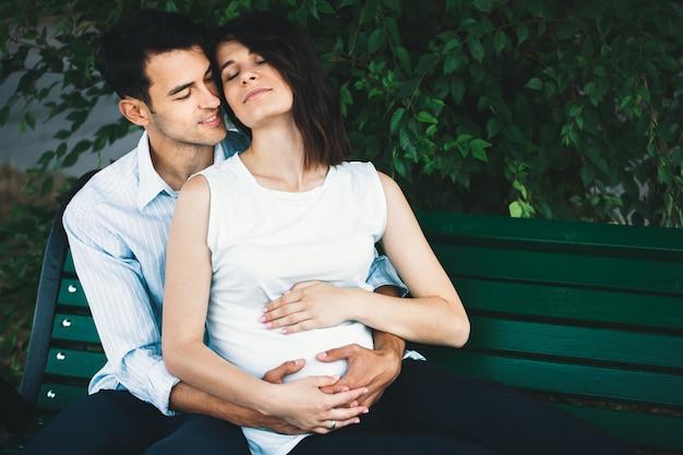 Mulher grávida tocando as mãos do marido