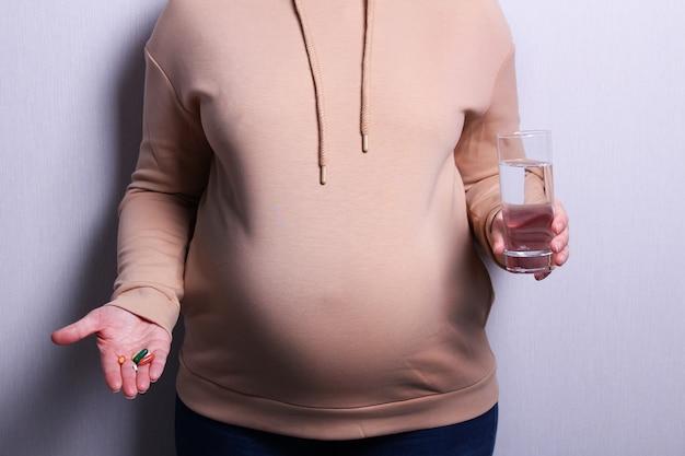 Mulher grávida tomando pílulas durante a gravidez. imagem de gravidez e maternidade.
