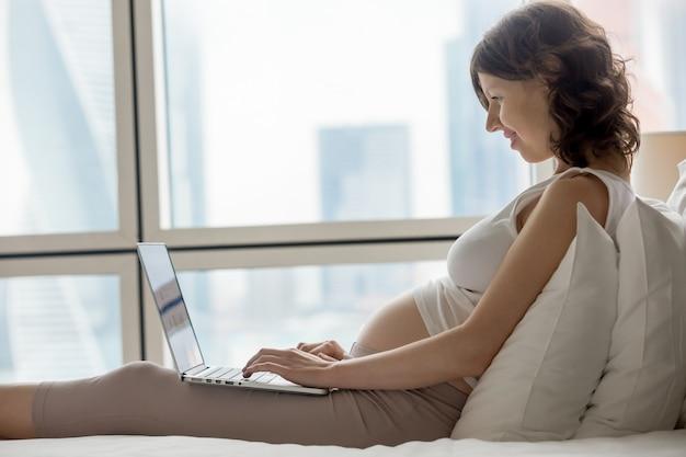 Mulher grávida trabalhando em casa