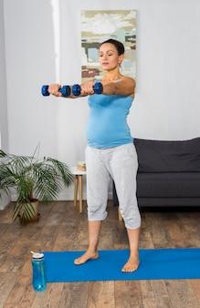 Mulher grávida treinando com pesos em casa no tapete