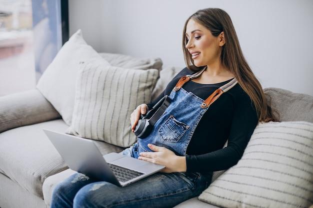 Mulher grávida usando computador em casa
