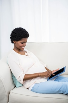 Mulher grávida, usando, tabuleta, ligado, sofá