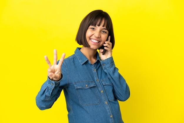 Mulher grávida usando telefone celular isolado em um fundo amarelo feliz e contando três com os dedos