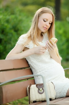 Mulher grávida usando telefone celular
