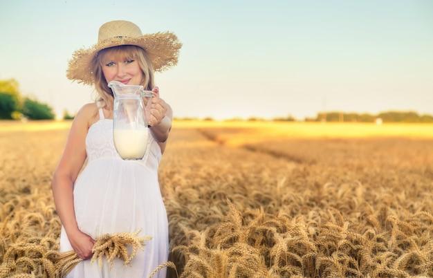 Mulher grávida usando vestido branco e segurando uma jarra de leite em um campo de trigo