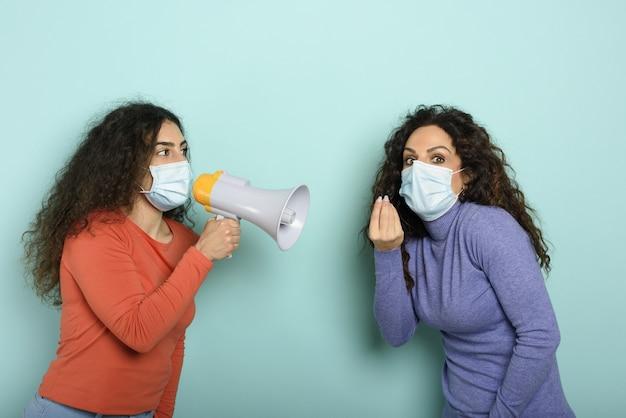 Mulher grita com alto-falante para um amigo, mas é difícil entender com máscara facial.