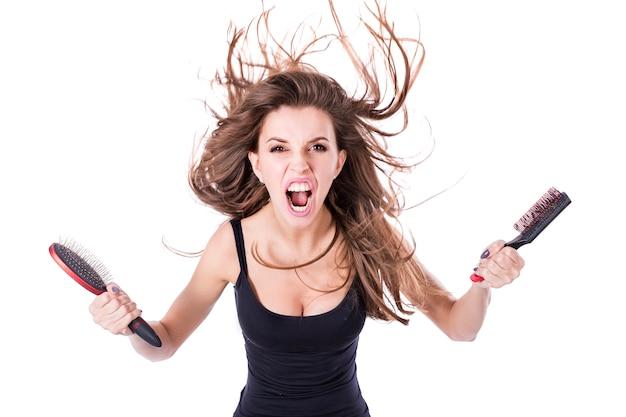 Mulher grita irritada com cabelos emaranhados voadores e pentes ina nas mãos. cuidados com os cabelos e o conceito de saúde