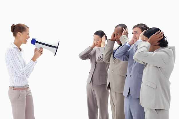 Mulher gritando alegremente em pessoas de negócios cobrindo seus ouvidos com as mãos