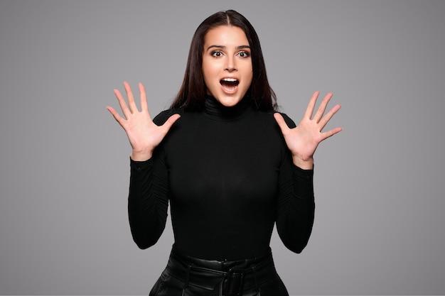 Mulher gritando animada com emoções fasciais em pé isolado sobre um fundo cinza isolado. foto de alta qualidade
